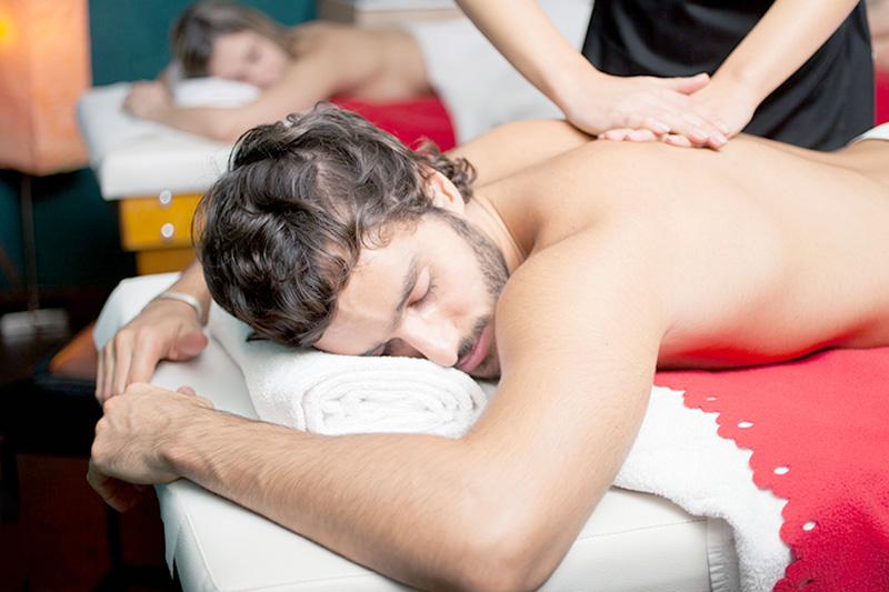 Leistungen Massagen - Ein Mann liegt auf einer Liege und wird von einer Physiotherapeutin massiert.
