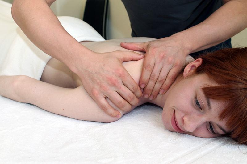 Physiotherapie - Eine Frau wird von einem Physiotherapeuten behandelt.