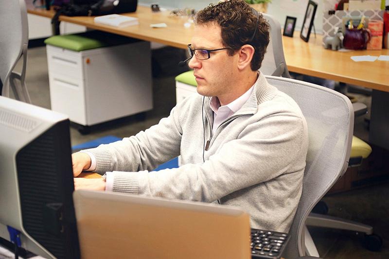 prävention arbeitsplatzoptimierung - Ein Mann sitzt an einem optimierten Arbeitsplatz am Computer