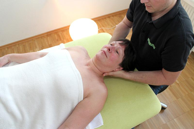Osteopathie Behandlung in Stuttgart. Frau liegt auf einer Liege und wird von einem Osteopathen behandelt.